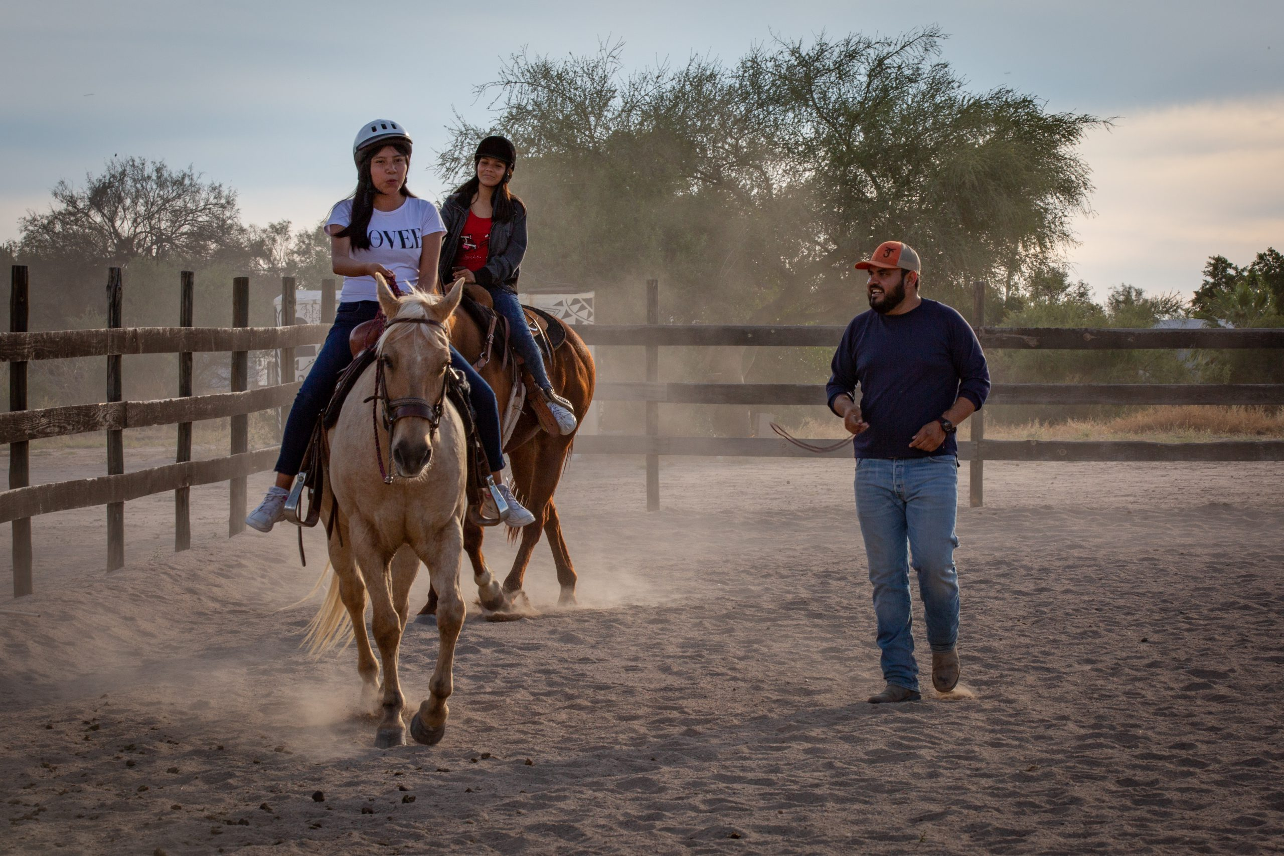 Two teen girls ride horses during equine program. This is one way Rancho el Camino does missions in Mexico