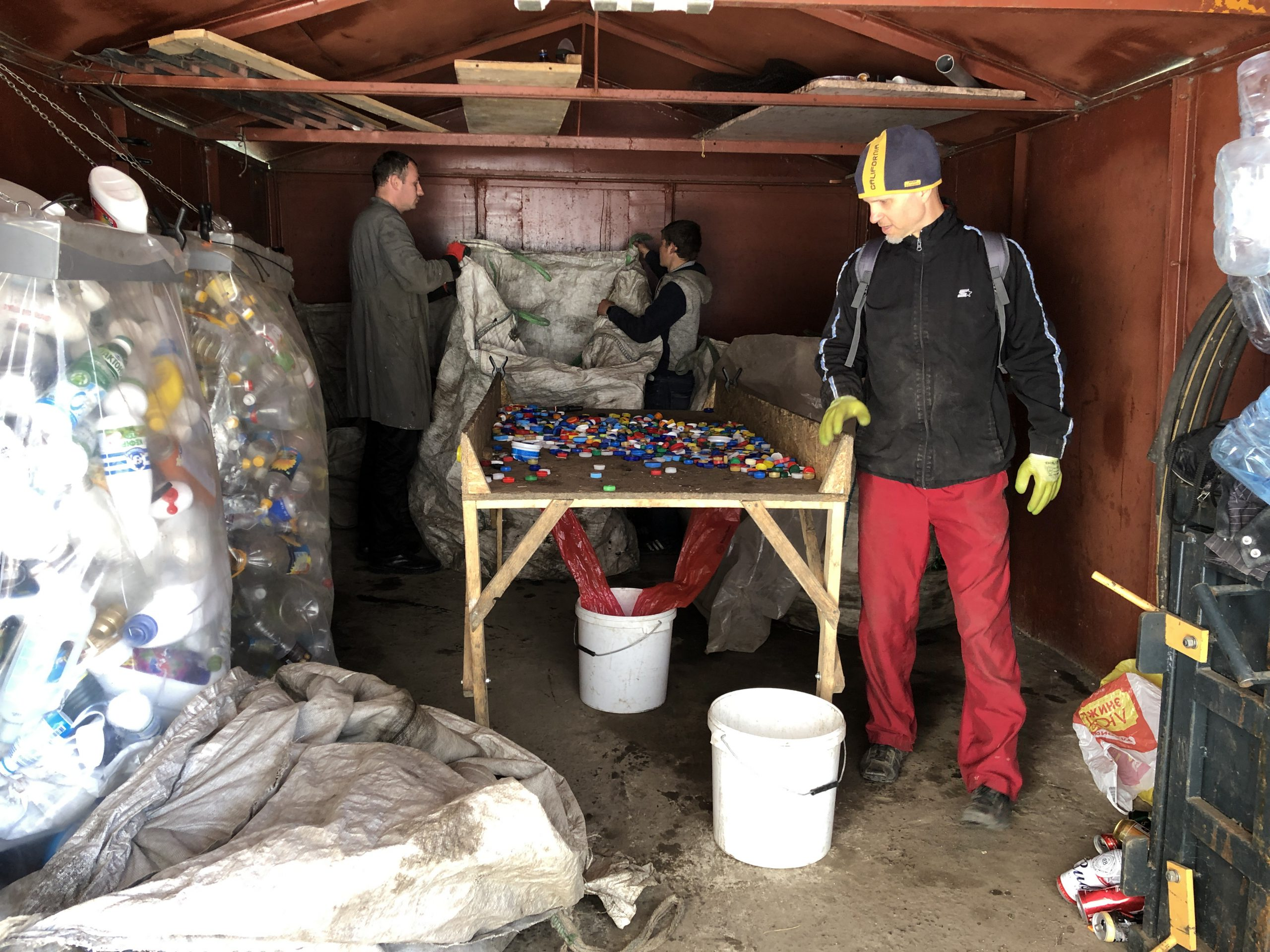 Men sort bottle caps as part of recycling project