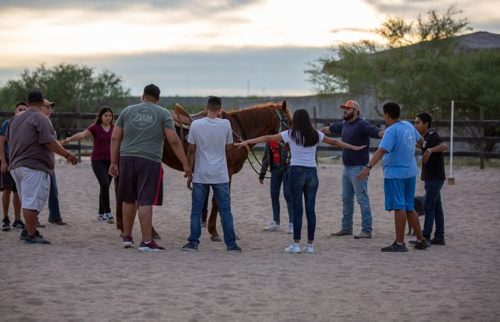 Teens stand in a circle around a horse at Rancho el Camino, where many short-term missionaries serve