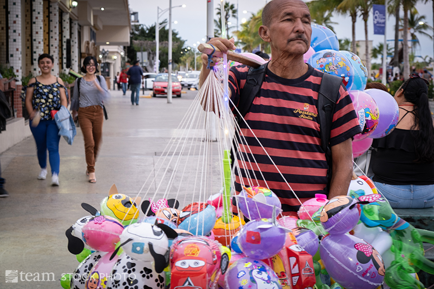 A man holds various children's' balloons for sale.