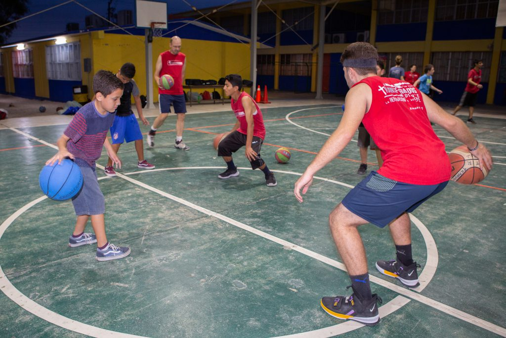 Mexican children play basketball at Transformados