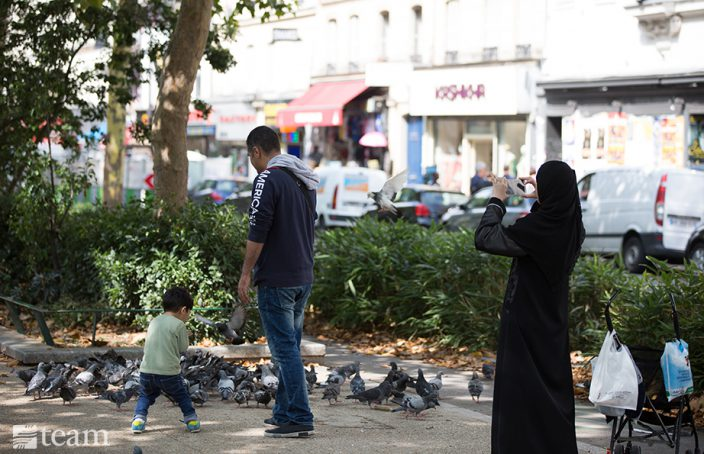 Muslim woman stands in French park, representing a situation in which cross-cultural training would be vital