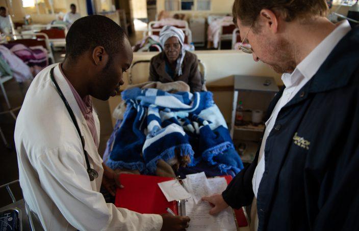 Two Karanda Mission Hospital doctors look at a patient's chart.