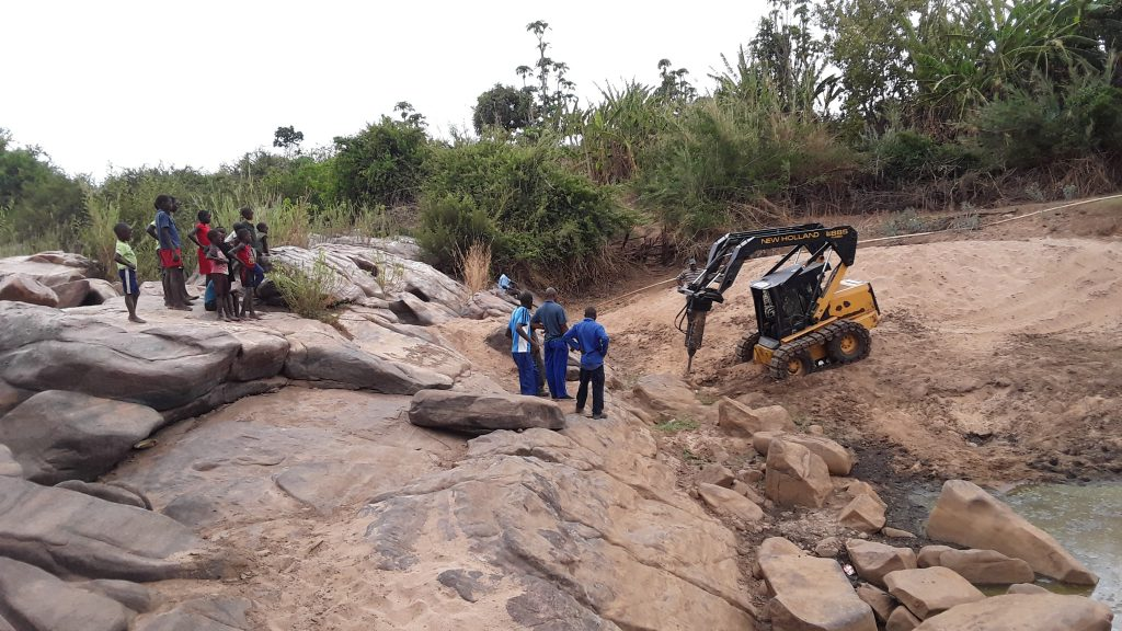 Local staff learn how to use a machine to break up rocks that block water flow for the hospital.
