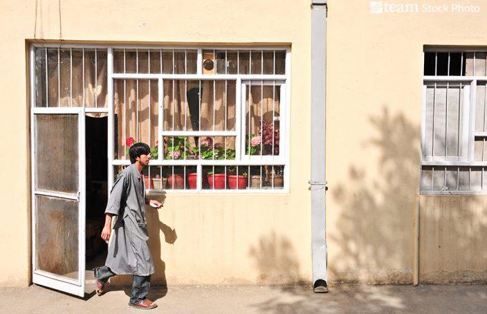A Middle Eastern man walks outside