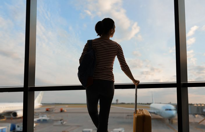Woman with suitcase looking out airport window